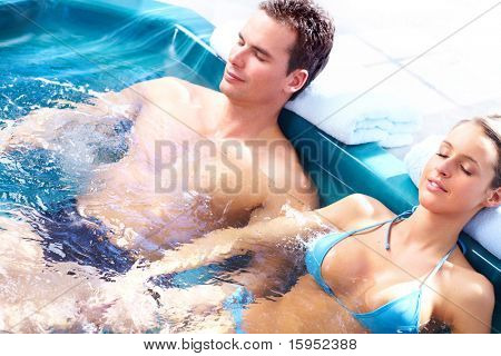 Young loving couple relaxing in a comfortable  jacuzzi.