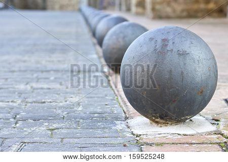 Closeup image of a grey rusty round bollard separating road from sidewalk.