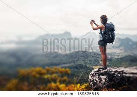 Young woman hiker with backpack standing on top of the mountain and taking a picture of valley