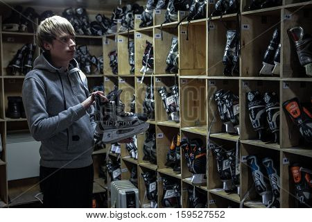 Saint-Petersburg Russia - December 2 2016: Urban outdoor ice rink in the park. rental item Shelves with skates. Man gives skates.