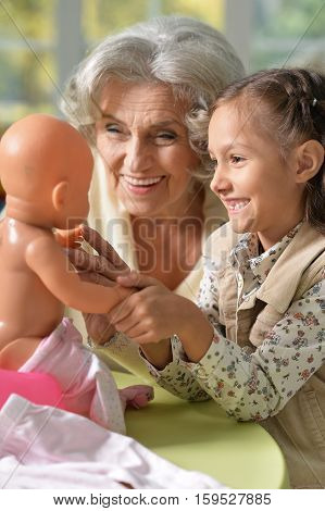 Portrait of grandmother and child play with baby doll