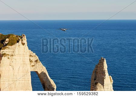 Scenic View Of Etretat With A Plane Flying Over Cliffs