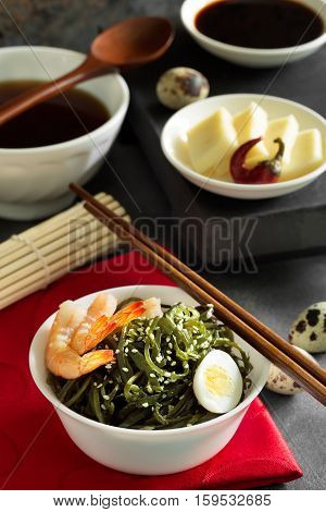 Delicious fresh seaweed salad with quail egg and seasame