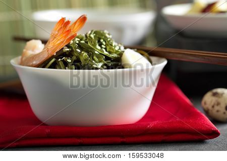 Delicious fresh seaweed salad with quail egg and seasame in the bowl on the red napkin