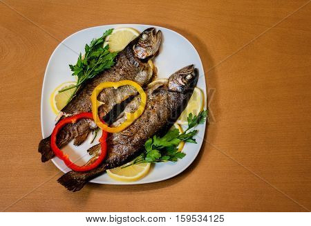 Two baked trouts with parsley on wooden background