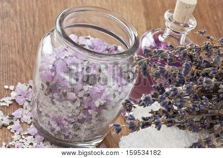 Aromatic sea salt lavender dried flower essential oil and soft towel on wooden background