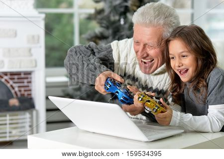 Portrait of happy grandfather and child playng video games