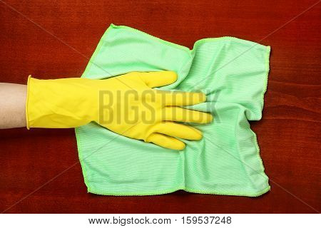 hand in rubber glove with microfiber cloth wiping the table