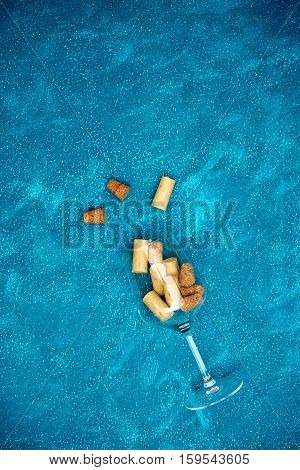 Wine Glass With Corks Over Blue Background.