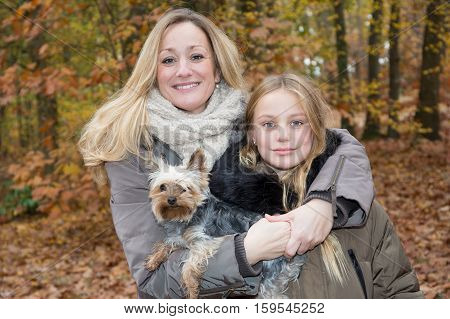 mother and daughter in the autumn park with little dog