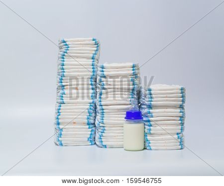 Pile of diapers and baby bottles on white background
