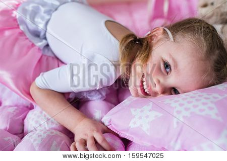 Happy child in a teepee tent. Little girl playing in a tent.