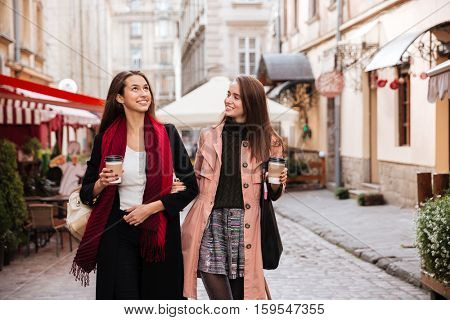 Two smiling pretty young women walking and drinking coffee in old town
