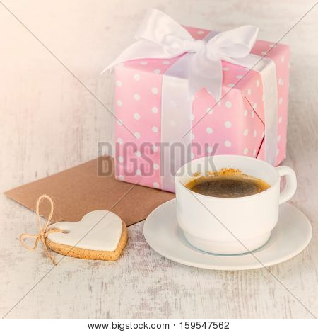 Gift box wrapped in pink dotted paper heart shaped love cookie a cup of coffee and an empty kraft card over a white wood background.