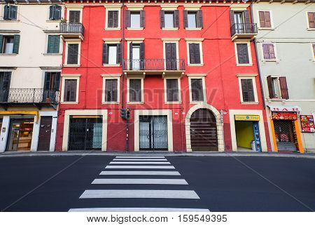 VERONA, ITALY- September 08 2016: The crosswalk and traffic light with red light in the Verona and the narrow sidewalk of the street