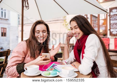 Two happy young women listening to music using earphones together in outdoor cafe