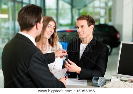 Sales situation in a car dealership, the young couple gets the key for the new car
