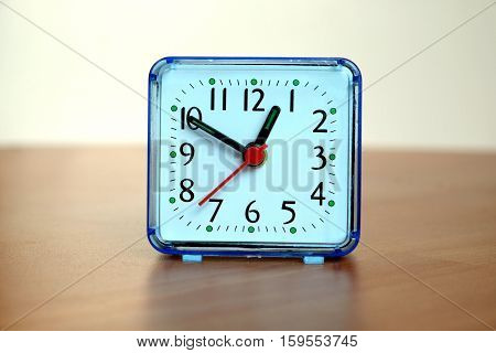 Table clock square shape showing one o'clock on front view closeup