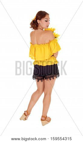 Gorgeous young woman in yellow blouse holding sunflowers looking over her shoulder standing isolated for white background.
