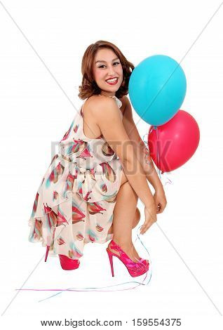 A beautiful young woman crouching on the floor holding two balloons isolated for white background.