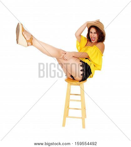 A lovely young woman posing in black shorts and yellow blouse with a cowboy hat lifting up booths legs isolated for white background.
