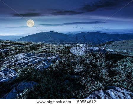 mountain summer landscape. meadow with huge stones among the grass on top of the hillside near the peak of mountain range at night in full moon light