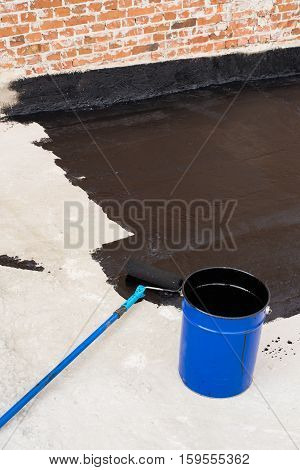 Roller brush. Worker covered surface bitumen primer for improving adhesion during surfacing rolled waterproofing during the installation of isolation on industrial or household objects.