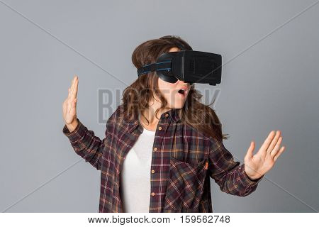 portrait of cute woman testing virtual reality glasses in studio on grey background