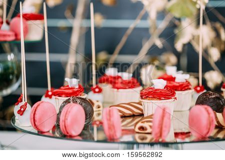 Dessert Sweet Tasty Cupcakes, Macarons And Cookies In Candy Bar On Table. Delicious Sweet Buffet. Wedding Holiday Decorations