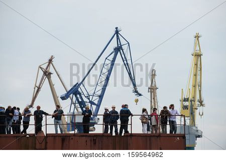 Shipyard Workers On The Wharf On A Background Of Cranes.