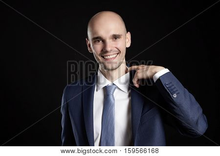 Studio shot of young man improves too tight collar.