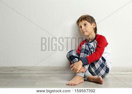 Cute little boy sitting on floor in empty room