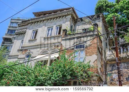 The old abandoned house with peeling paint and green trees in front of it at Santa Teresa district of Rio de Janeiro, Brazil