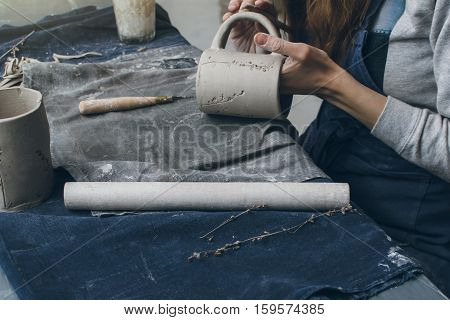 Woman making a cup with clay, ceramic workshop