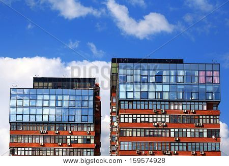 Office buildings with glass panels and air conditioning on the wall