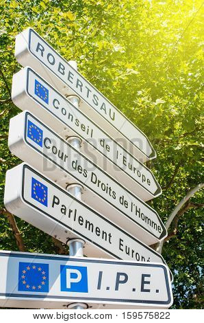Road sign in European Capital of Strasbourg on corner with direction to Council of Europe European Court of human Rights and European Parliament buildings on sunny summer day