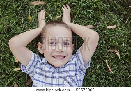 Happy little boy pretending to be a bunny laying on grass