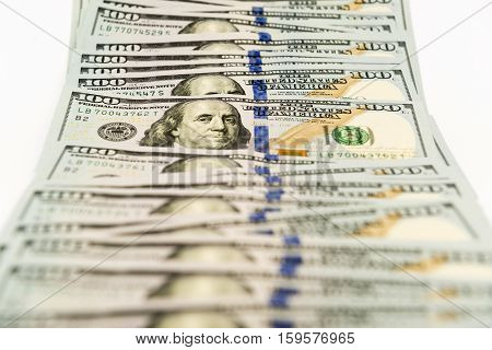 Many hundred dollar cash banknotes spread on white surface