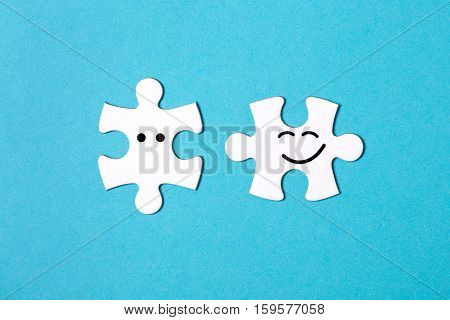 Two disconnected jigsaw puzzle pieces on blue background. One piece is happy to connect and another one is surprised. The concept of finding the right solutions in teamwork.