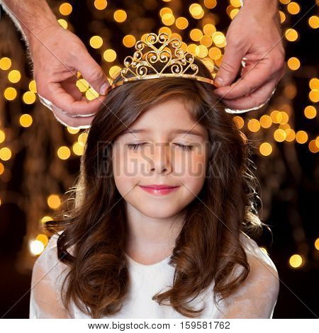 A little brunette girl getting crowned with a tiara in front of a starry background. She has closed eyes and looks pleased to be receiving her crown.