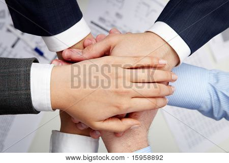 Image of business partners hands on top of each other symbolizing companionship and unity