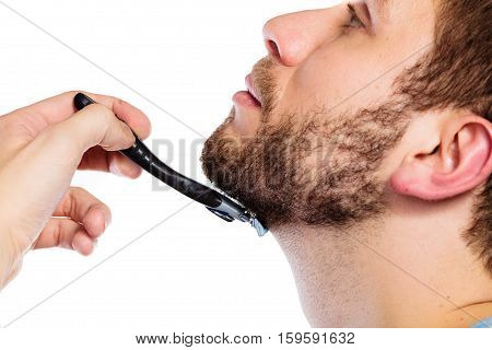 Health beauty and skin care concept. Closeup part of male face. Young man guy styling beard holding disposable blue razor blade white background.