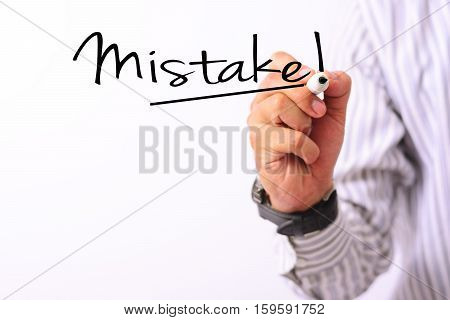 business concept image of a hand holding marker and write mistake isolated on white