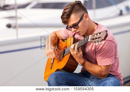 Romance music sound talent masculinity concept. Young guitarist sitting on pier. Man playing on guitar in front of boat.