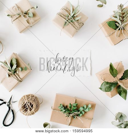 calligraphy words happy holidays and beauty arrangement frame of craft boxes and green branches on white background. flat lay top view