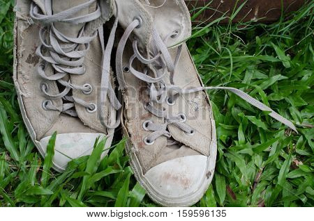 Lack of old shoes Placed on the beautiful green grass.