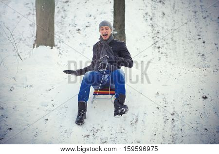 young man sledding with mountains  winter, cold