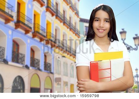 Brunette student young girl teen latin holding books colorful houses