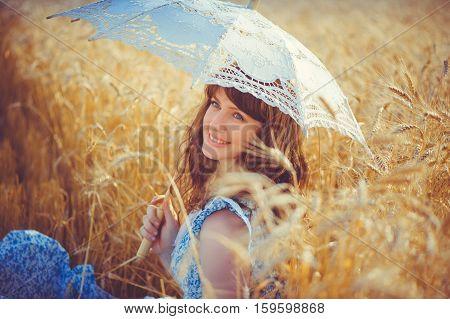 Smiling Girl Sitting In A Wheat Field Under A White Sun Umbrella