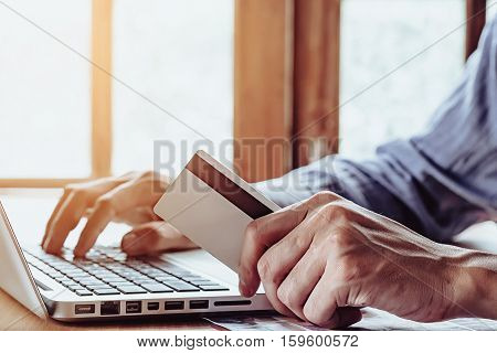 Young man hands holding a credit card and using laptop computer for online shopping.Online shopping concept.Hand holding credit card.Young man using laptop.